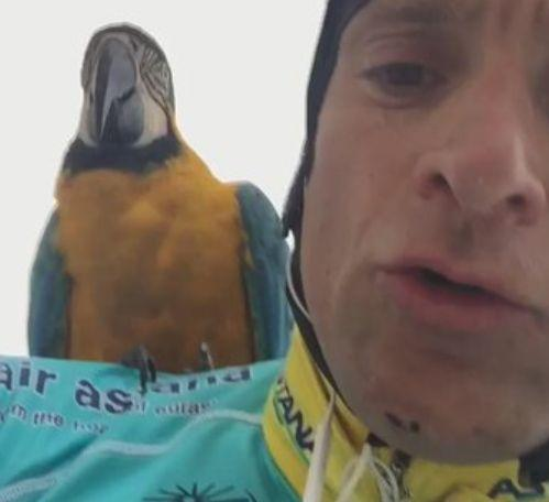 Michele Scarponi on a ride with Frankie the macaw (source Twitter).JPG