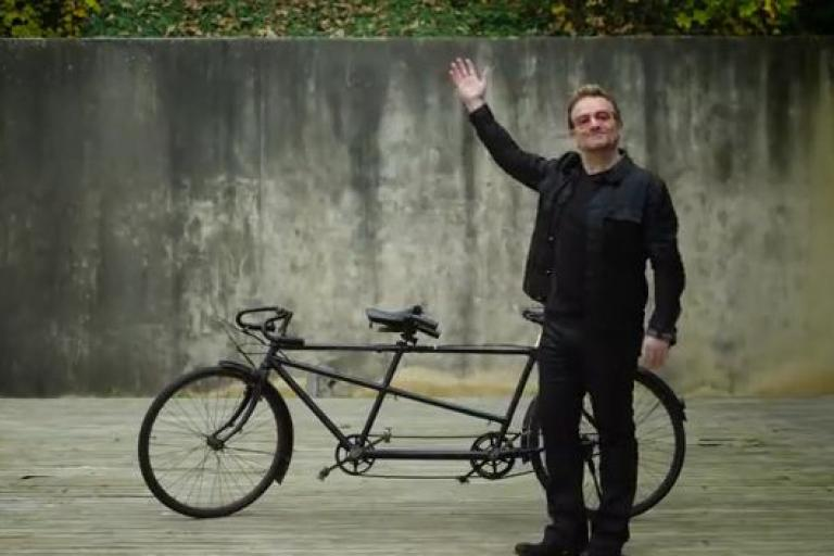 Bono and bike (source (RED) YouTube video still).JPG