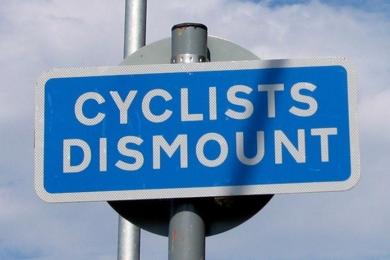 Cyclists dismount sign (CC licensed by Marcin Wichary via Flickr).jpg