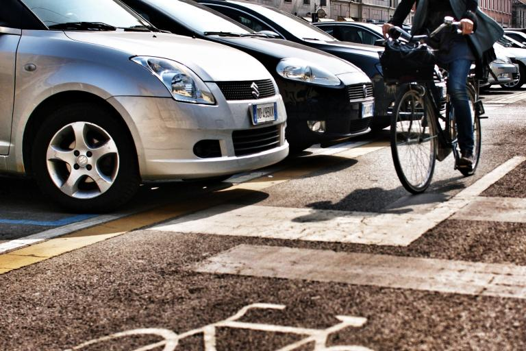 Cyclist passing parked cars in Milan (copyright Simon MacMichael)