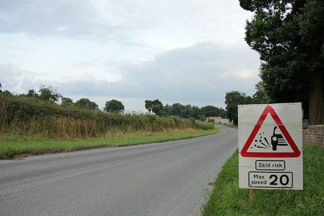 Road surface dressing loose chippings warning (licensed CC BY-2.0 by David Mitchell on Flickr).jpg