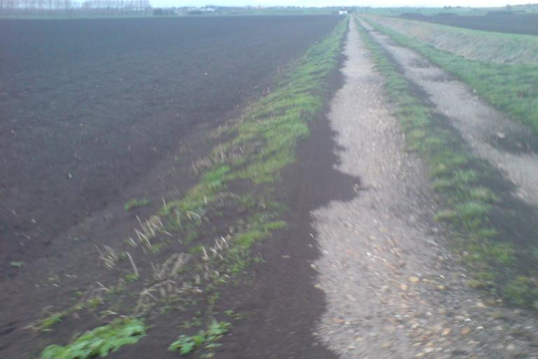 The topsoil blows onto the road in the recent storms