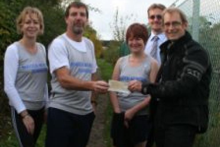 Phil England of Maiden Newton Running Club presents cheque to Peter Henshaw of Sustrans.JPG
