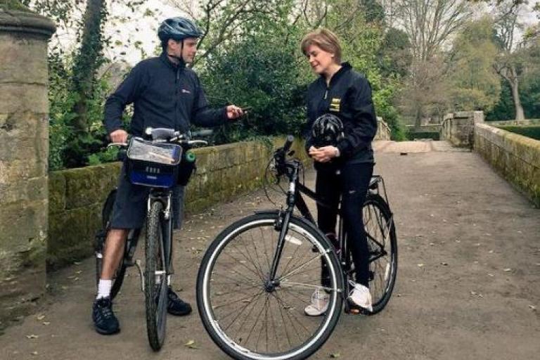 Nicola Sturgeon interviewed on bike (source Nicola Sturgeon Twitter, image cropped)