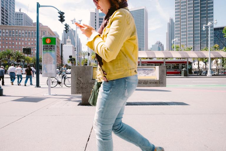 Pedestrian lookinng at phone (licensed CC BY 2.0 by Sonny Abesamis on Flickr)